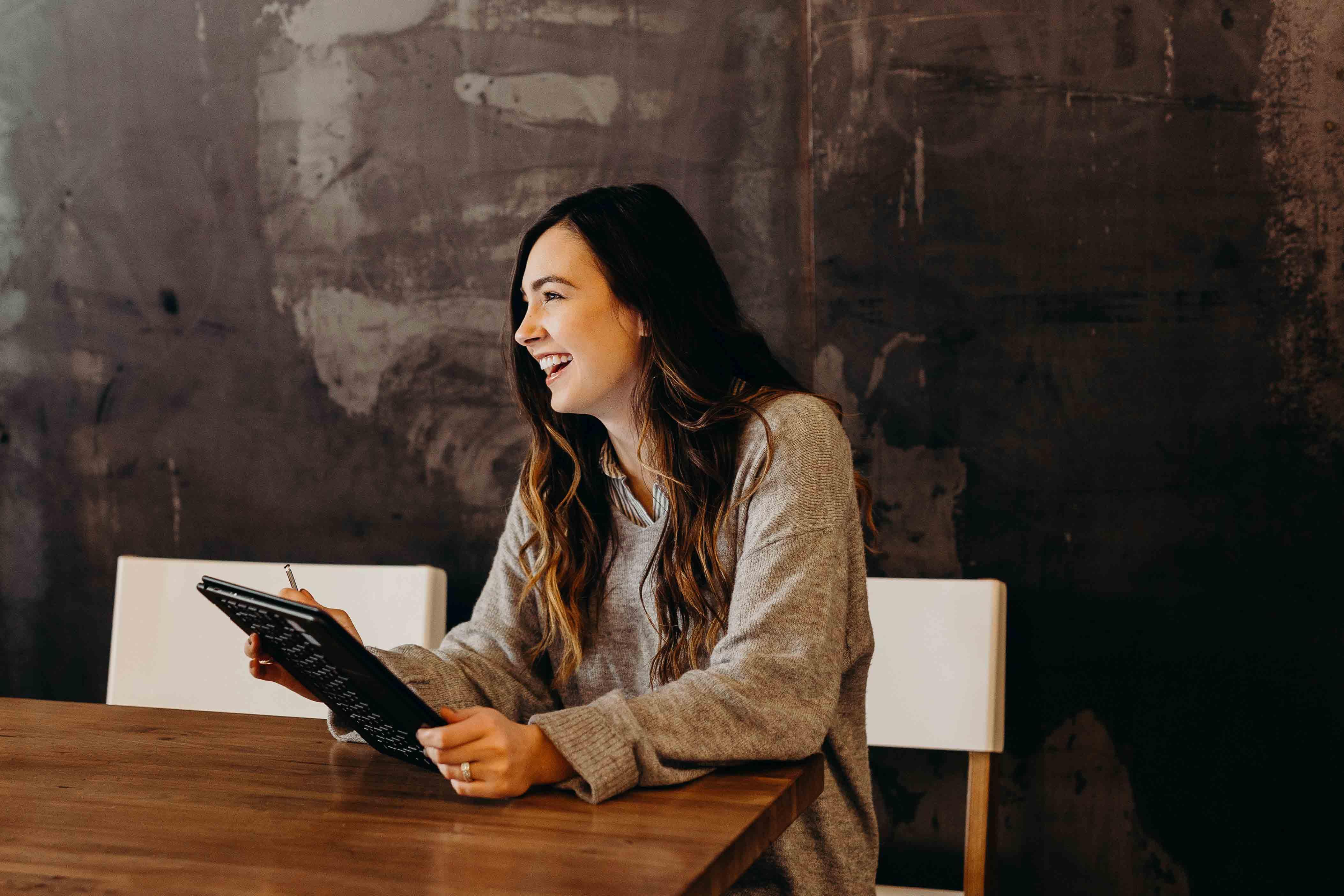 women laughing sitting at desk